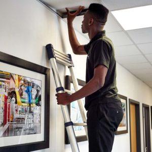 A man using an Xtend+Climb telescopic ladder to inspect a ceiling